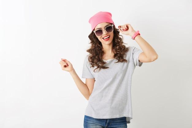 Retrato de uma mulher bonita alegre hipster com chapéu rosa, óculos de sol, sorrindo, humor feliz, isolado, humor positivo, dançando, tendência da moda jovem, rosto bonito