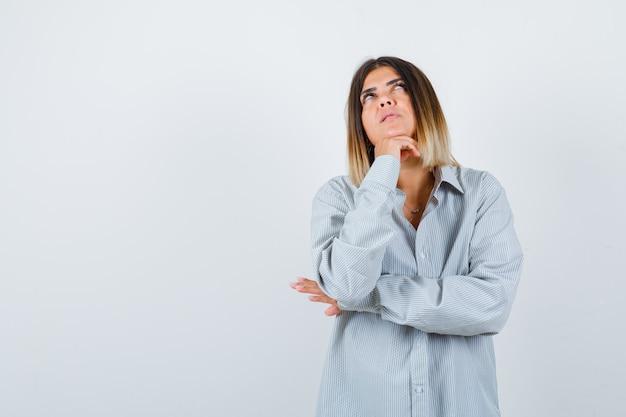 Retrato de uma mulher bonita apoiando o queixo na mão, olhando para cima com a camisa e olhando pensativamente para a frente