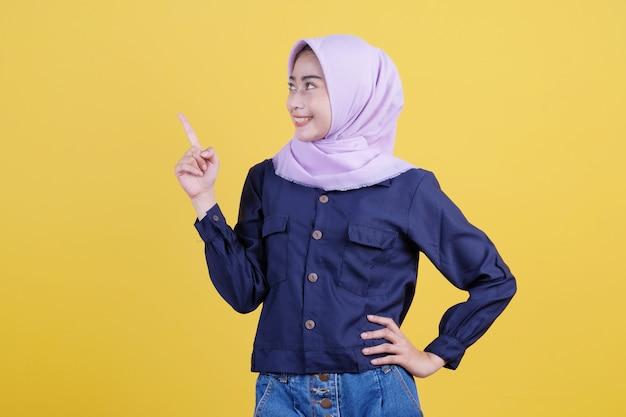 Retrato de uma mulher bonita apontando para cima em um pano casual, usando um hijab em fundo amarelo isolado