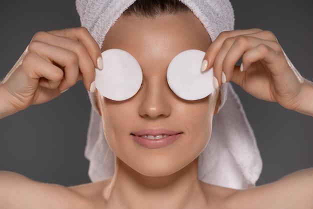 Retrato de uma mulher bonita atraente jovem sorridente com toalha na cabeça após o banho fazendo binóculos com duas almofadas de algodão branco tendo sorriso radiante isolar cinza