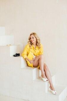 Retrato de uma mulher bonita, atraente, sorridente e charmosa em um terno amarelo de verão com fones de ouvido e um caderno amarelo. foco seletivo suave.
