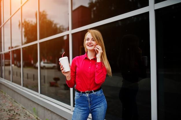 Retrato de uma mulher bonita blusa vermelha e calça jeans casual, falando no telefone celular e segurando uma xícara de café fora do enorme shopping center.