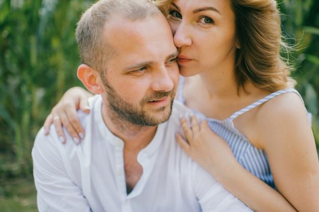Retrato de uma mulher bonita caucasiana com cabelo escuro curto em um vestido azul com seu marido forte relaxa juntos no milharal da aldeia.