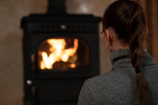 Retrato de uma mulher bonita caucasiana passando um tempo em casa à noite perto da lareira