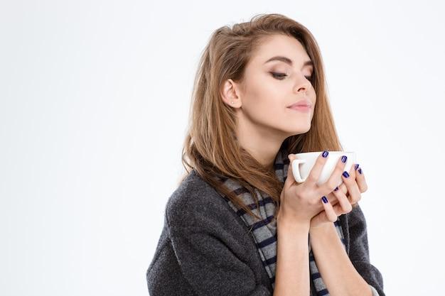 Retrato de uma mulher bonita cheirando a xícara com café isolado em um fundo branco