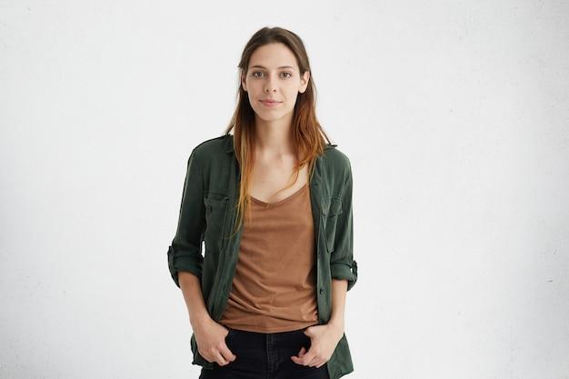 Retrato de uma mulher bonita com aparência europeia com rosto oval, olhos escuros atraentes e cabelos longos e lisos, vestida casualmente, sentindo-se relaxada em pé com as mãos nos bolsos
