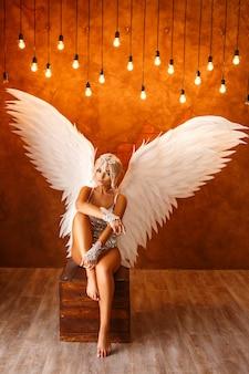 Retrato de uma mulher bonita com asas de anjo branco na