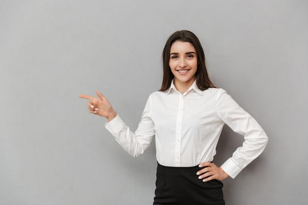 Retrato de uma mulher bonita com cabelos castanhos compridos em camisa branca sorrindo e apontando o dedo de lado na copyspace, isolado sobre uma parede cinza