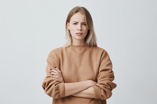 Retrato de uma mulher bonita com cabelos loiros lisos, franzindo a testa o rosto em desagrado, vestindo blusa de mangas compridas solta, mantendo os braços cruzados. mulher jovem e atraente em postura fechada.