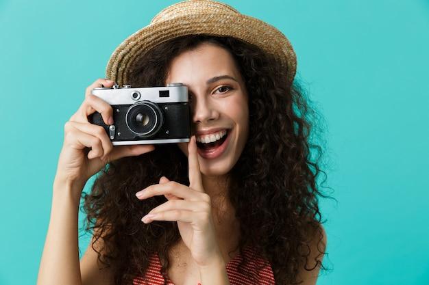 Retrato de uma mulher bonita com chapéu de palha fotografando na câmera retro, isolado sobre a parede azul