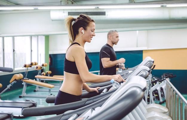 Retrato de uma mulher bonita com fones de ouvido, definindo o painel de controle da esteira para treinamento no centro de fitness. conceito de esporte e tecnologia.