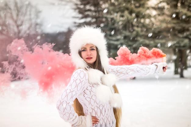 Retrato de uma mulher bonita com fumaça vermelha ao redor