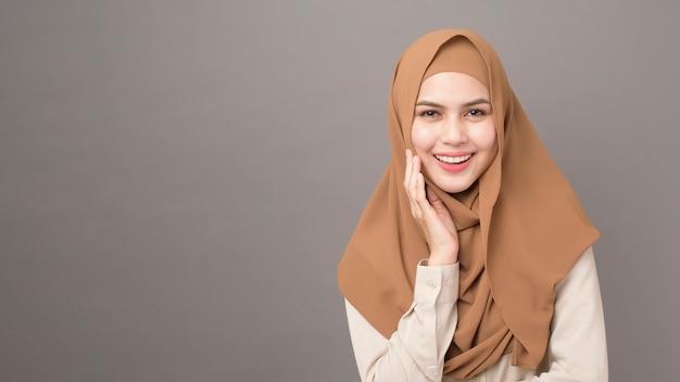 Retrato de uma mulher bonita com hijab está sorrindo em cinza
