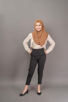 Retrato de uma mulher bonita com hijab está sorrindo em fundo cinza
