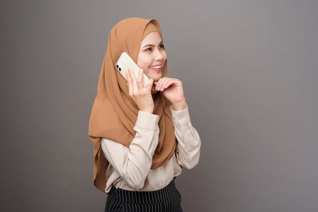 Retrato de uma mulher bonita com hijab usando celular na parede cinza