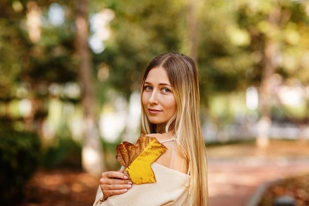 Retrato de uma mulher bonita com longos cabelos loiros ao ar livre