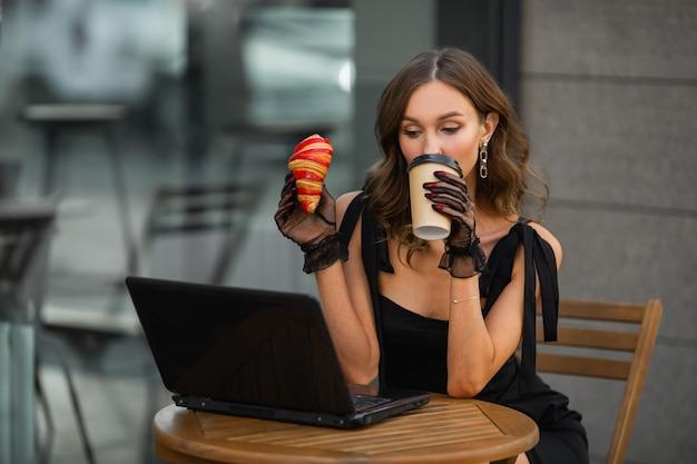 Retrato de uma mulher bonita com maquiagem atrás de um laptop com uma xícara de café