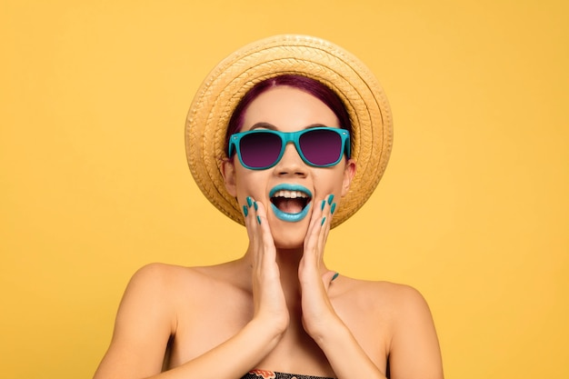 Retrato de uma mulher bonita com maquiagem brilhante, chapéu e óculos de sol em fundo amarelo studio. estilo e penteado elegante e moderno. conceito de beleza, moda e publicidade. parece chocado, surpreso.