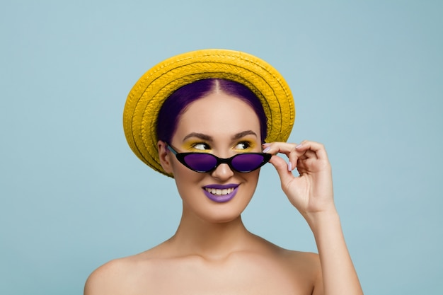 Retrato de uma mulher bonita com maquiagem brilhante, chapéu e óculos de sol no estúdio azul