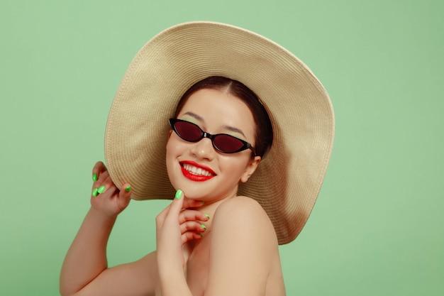 Retrato de uma mulher bonita com maquiagem brilhante, chapéu e óculos escuros sobre fundo verde do estúdio. estilo e penteado elegante e moderno. cores do verão. conceito de beleza, moda e publicidade. sorridente.