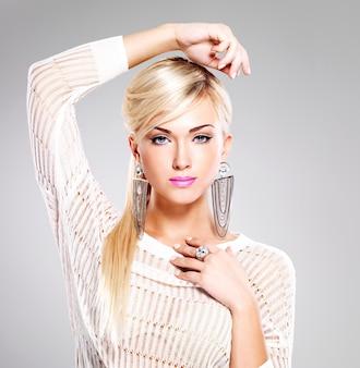 Retrato de uma mulher bonita com maquiagem brilhante e cabelos brancos compridos.