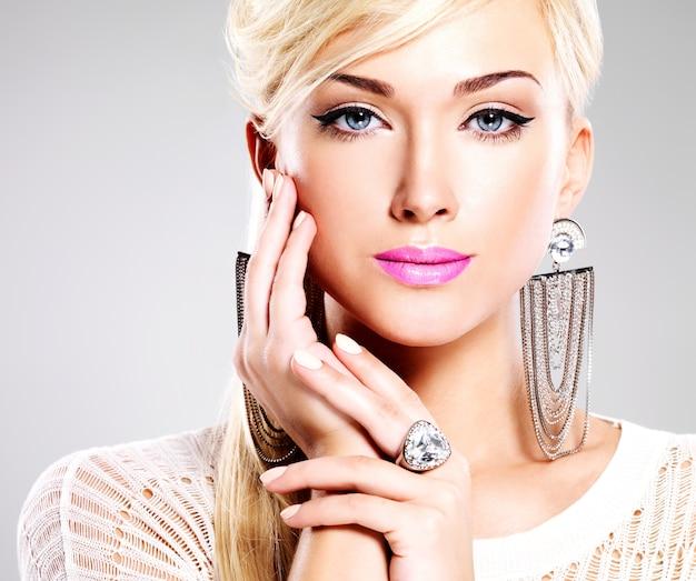 Retrato de uma mulher bonita com maquiagem brilhante e cabelos brancos.