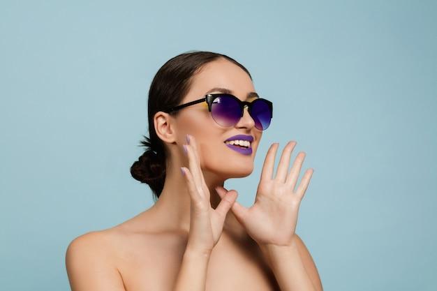 Retrato de uma mulher bonita com maquiagem brilhante e óculos de sol no estúdio azul