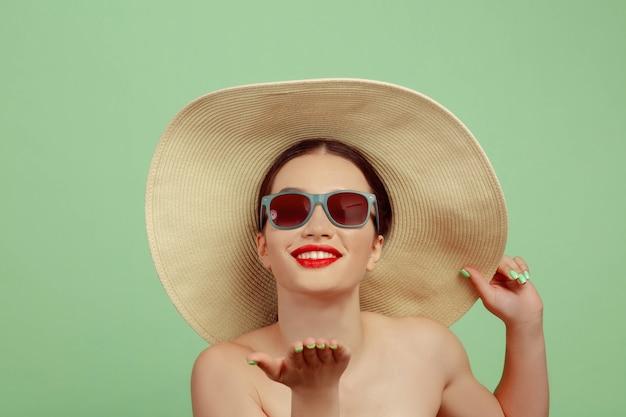 Retrato de uma mulher bonita com maquiagem brilhante, óculos vermelhos e chapéu no estúdio verde