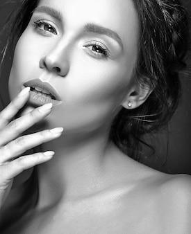 Retrato de uma mulher bonita com maquiagem diária fresca tocando sua boca