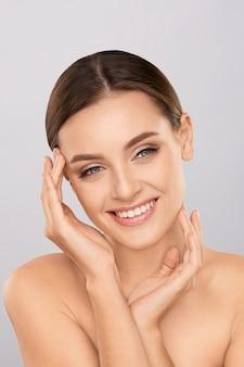 Retrato de uma mulher bonita com maquiagem natural tocando seu rosto. jovem de beleza com pele limpa fresca e perfeita. conceito de cuidados com a pele. cosmetologia, beleza e spa. tratamento facial. pele natural.