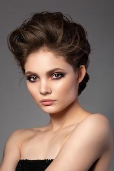 Retrato de uma mulher bonita com maquiagem romântica nos olhos esfumados em vermelho e dourado