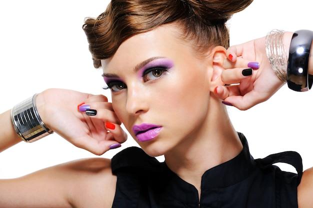 Retrato de uma mulher bonita com maquiagem roxa nos olhos e lábios