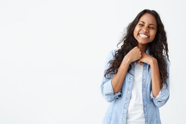 Retrato de uma mulher bonita com pele limpa escura e sorriso lindo, rindo em voz alta de piada enquanto se diverte dentro de casa com os amigos, fechando os olhos de alegria, parecendo despreocupado e relaxado.