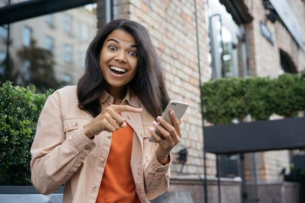 Retrato de uma mulher bonita com rosto emocional usando telefone celular, compras online com dinheiro de volta