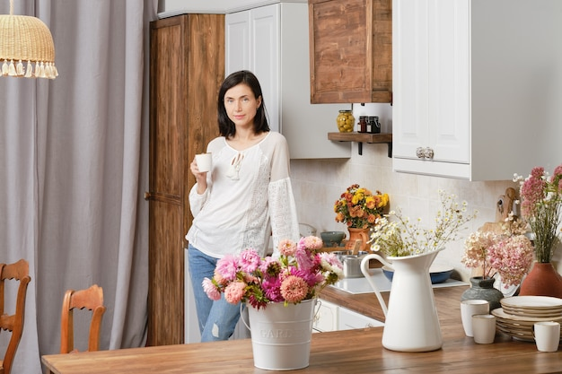 Retrato de uma mulher bonita com roupas casuais na cozinha com uma xícara de café na mão