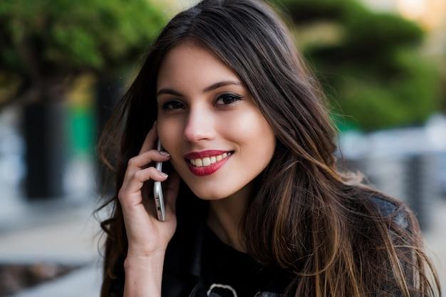 Retrato de uma mulher bonita com sorriso branco perfeito falando no telefone celular ao ar livre
