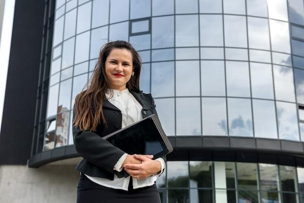 Retrato de uma mulher bonita com tablet ao ar livre perto de um grande escritório