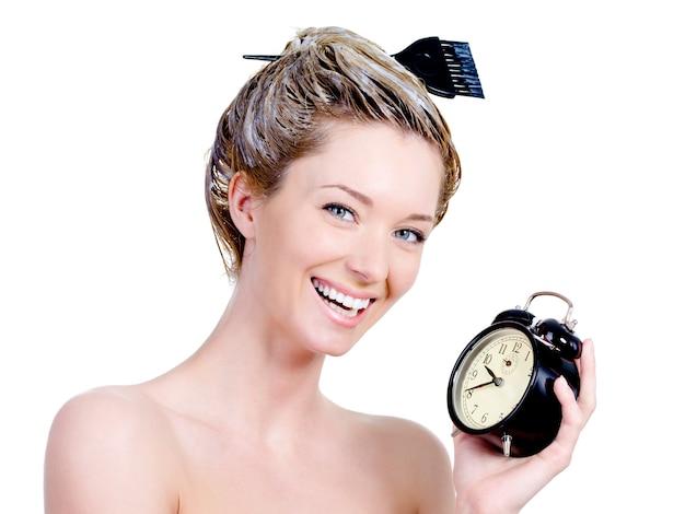 Retrato de uma mulher bonita com tintura no cabelo e segurando um relógio - isolado no branco