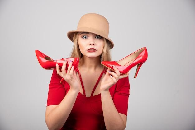 Retrato de uma mulher bonita com um par de saltos, olhando para a câmera.