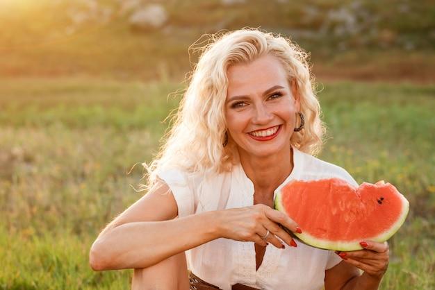 Retrato de uma mulher bonita com um pedaço de melancia na mão na natureza alegre