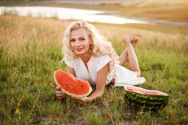 Retrato de uma mulher bonita com um pedaço de melancia na mão na natureza