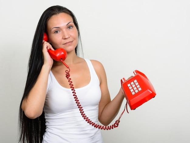 Retrato de uma mulher bonita com um telefone antigo contra uma parede branca