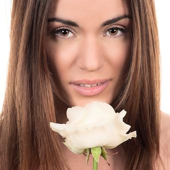 Retrato de uma mulher bonita com uma rosa branca em fundo branco