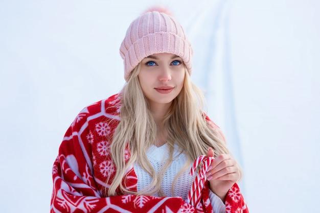 Retrato de uma mulher bonita contra a neve em um chapéu rosa e manta vermelha posando para a câmera