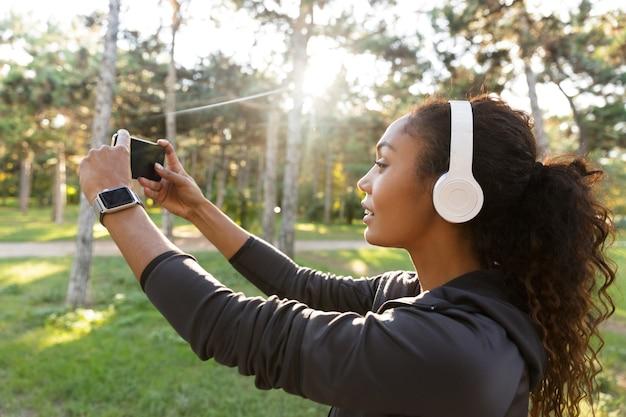 Retrato de uma mulher bonita de 20 anos usando um agasalho esportivo preto e fones de ouvido, tirando uma foto de selfie no celular enquanto caminha pelo parque verde