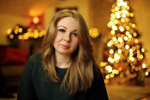 Retrato de uma mulher bonita de 30 anos em um interior festivo de ano novo