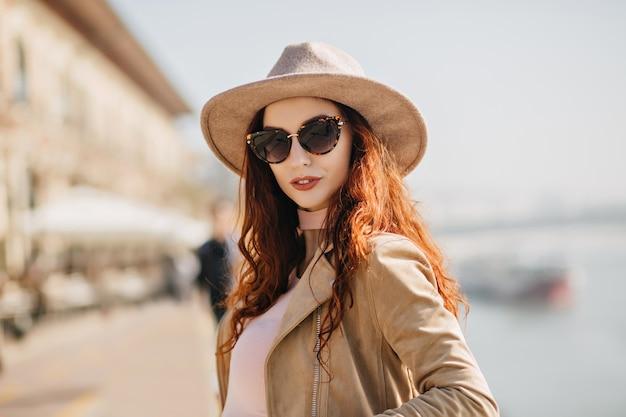 Retrato de uma mulher bonita de cabelo escuro com pele branca em pé na parede do rio