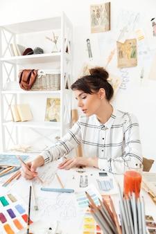 Retrato de uma mulher bonita designer de moda, trabalhando na oficina