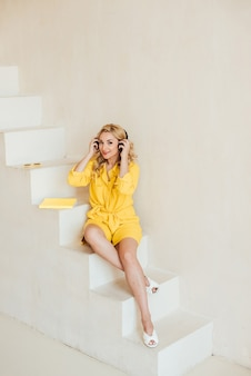 Retrato de uma mulher bonita e atraente em um terno amarelo de verão e fones de ouvido, ouvindo música. foco seletivo suave.
