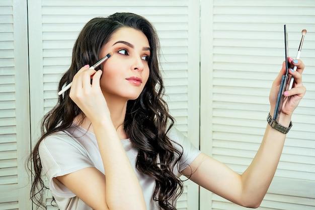Retrato de uma mulher bonita e atraente maquiadora visagiste blogueira de beleza sentada em frente a um espelho e aplica maquiagem cosmética sombra no rosto em estúdio de salão